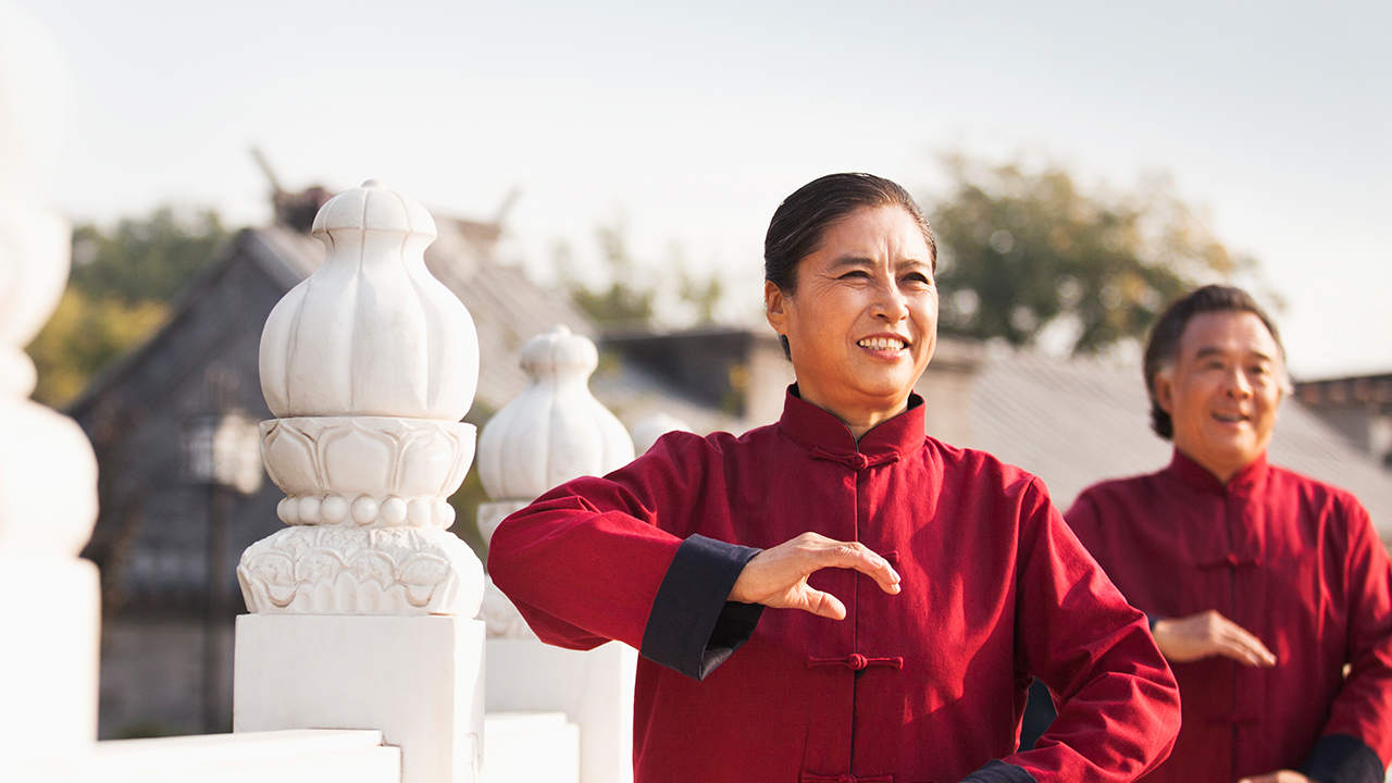Asian couple doing Tai Chi at a temple; image used for HSBC Foreign Currency Term Deposit page.