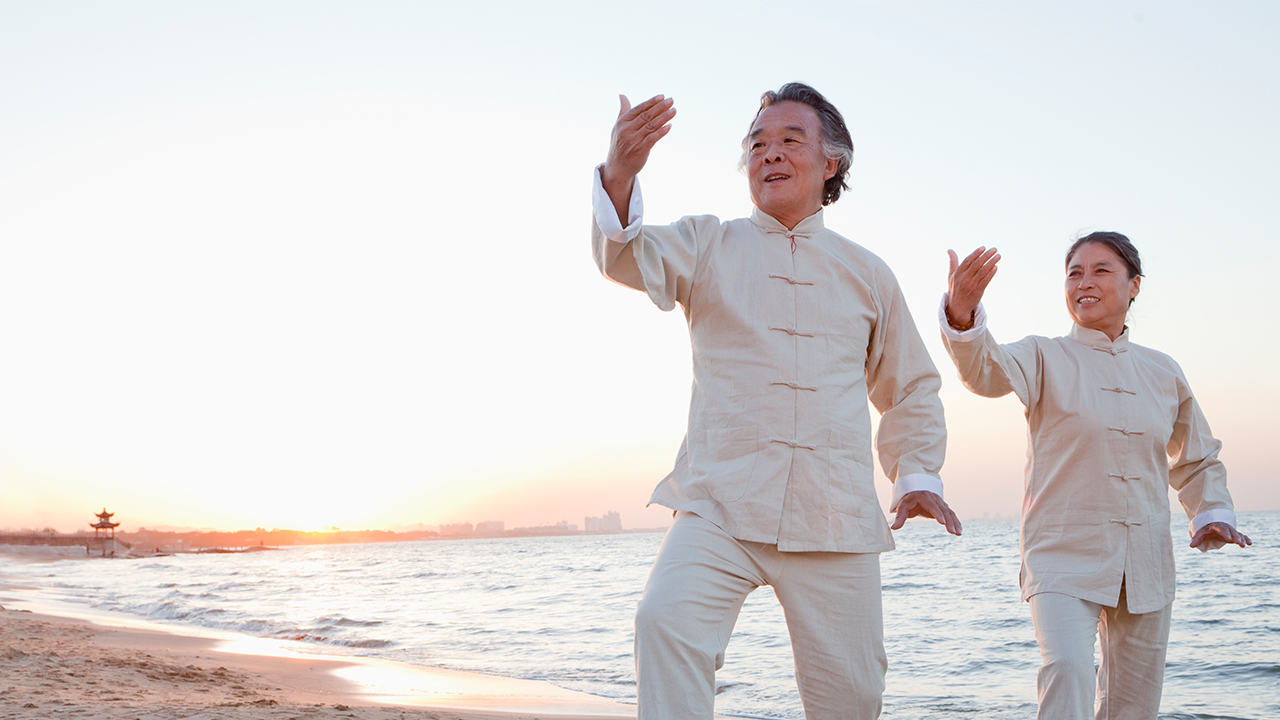 Asian couple doing Tai Chi on beach; image used for HSBC Term Deposit Account page