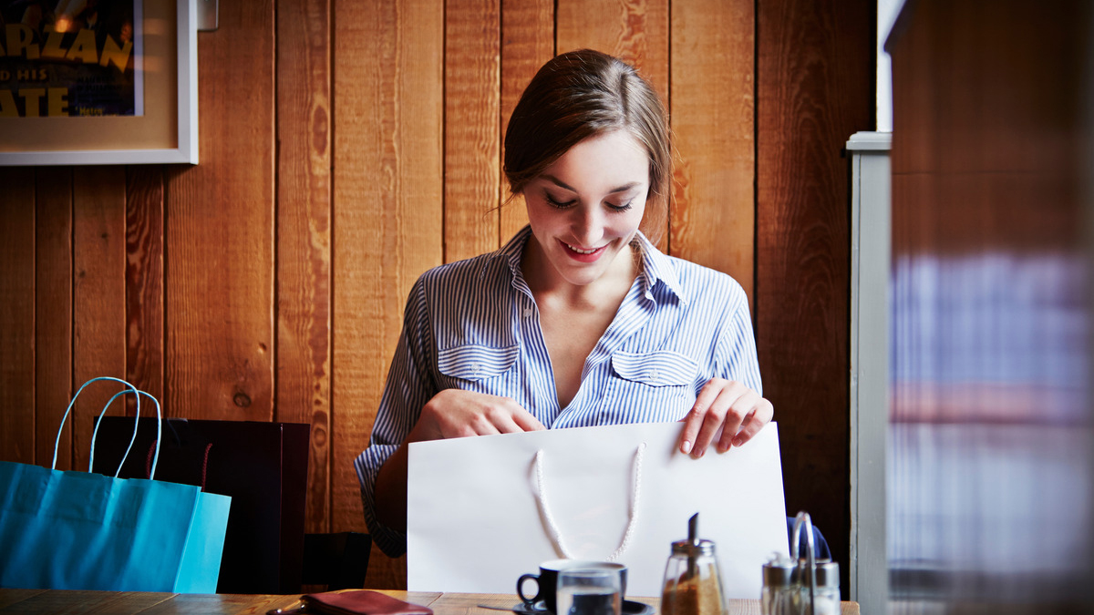 Woman looking into a shopping bag at a cafe; image used for HSBC Low Rate Card page.