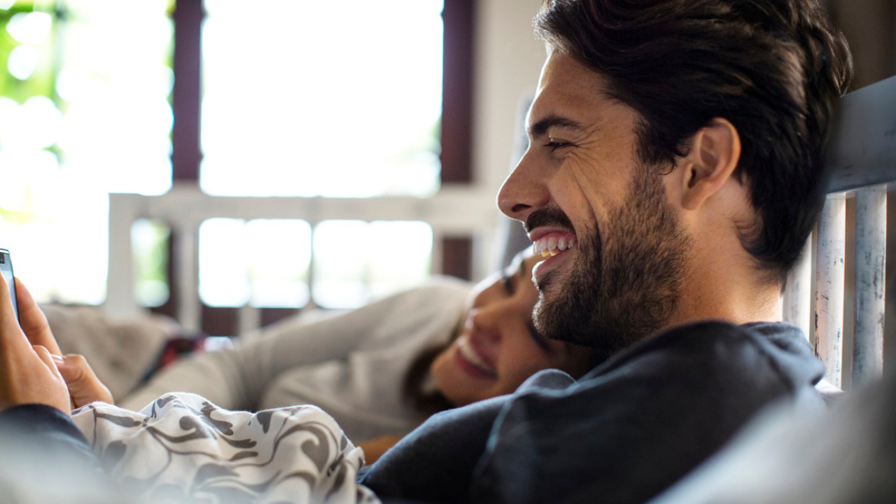 A couple is smiling in the sofa with coffee; image used for HSBC Australia Accounts page.