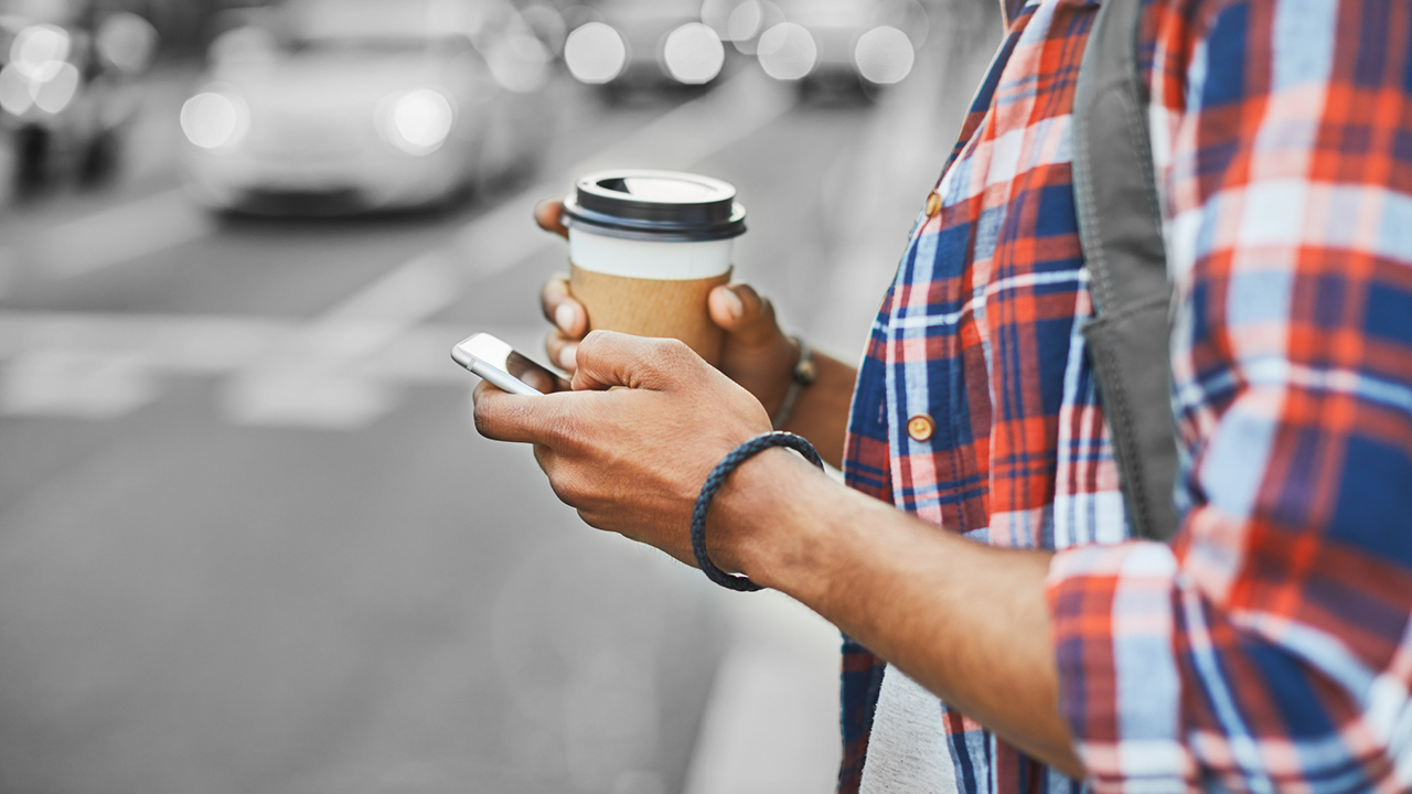 A man holding a cup of coffee and using mobile; image used for HSBC Australia mobile banking.
