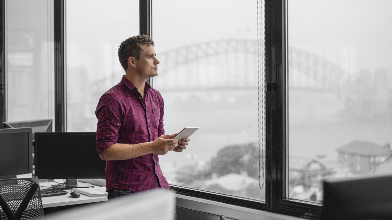 A man holding tablet and staring out of window; image used for HSBC Foreign Currency Flexi Saver Account page.