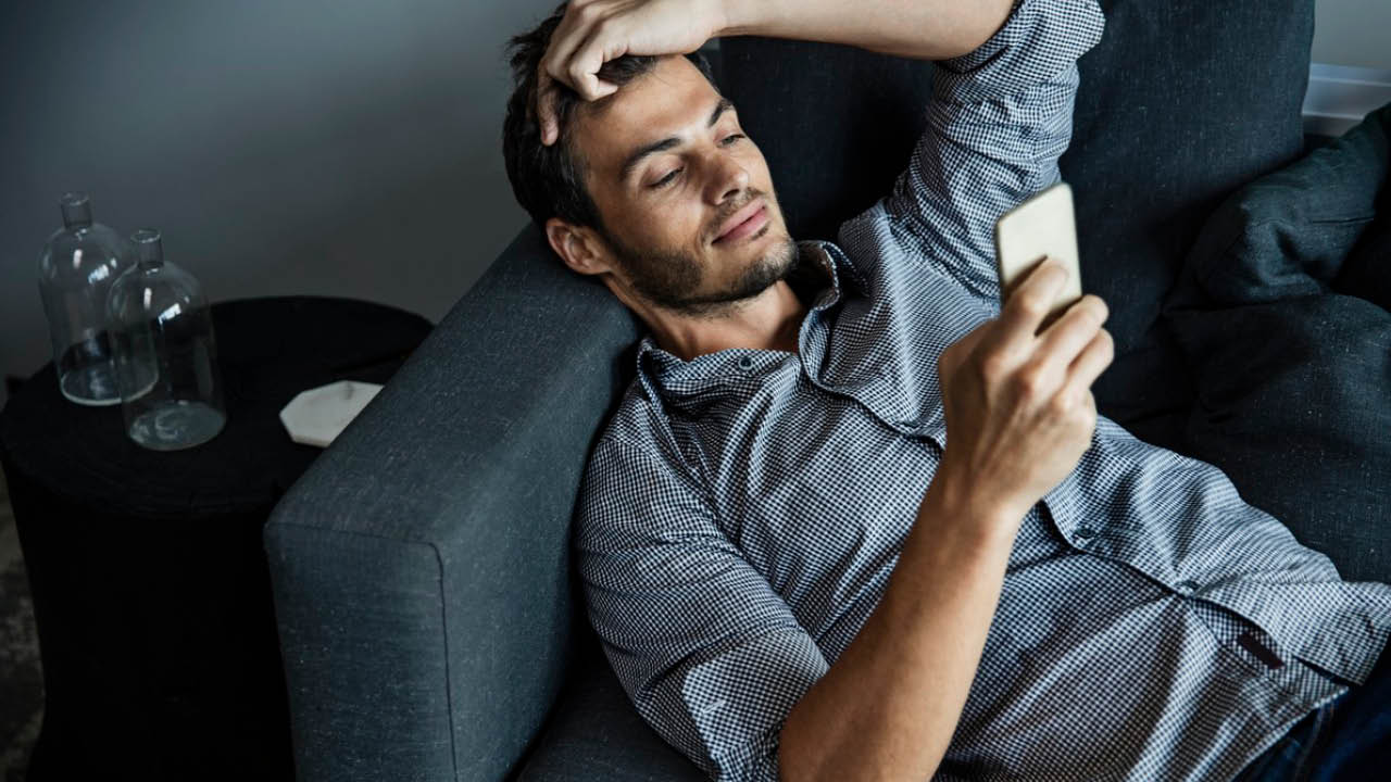 A man using phone on sofa; image used for HSBC Credit Cards Balance Transfers  offer page.