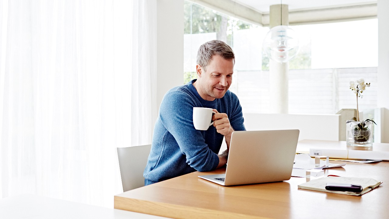 A man using computer with a coffee in his hand; image used for HSBC SecureMail.