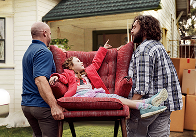 Two men moving a couch with a little girl sitting on it into a house; image used for HSBC Australia's Home Loans product.
