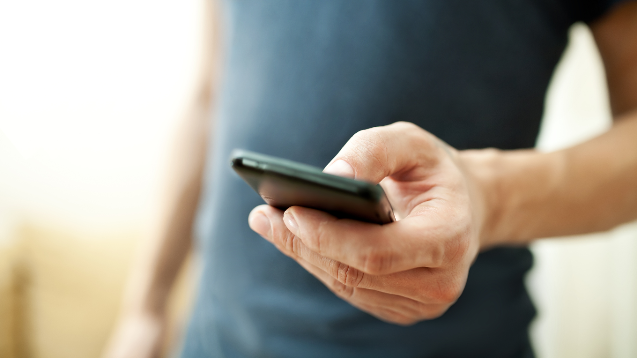 A man holding a smartphone on hand; image used for HSBC Safeguard.