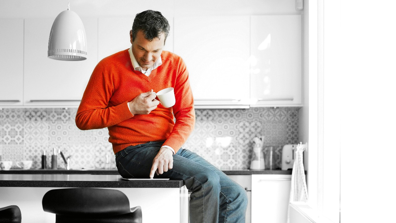 A person using tablet and holding a coffee mug on hand; image used for HSBC Foreign Currency Compare Accounts.