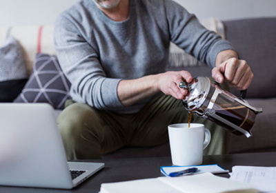 A man pouring coffee at home; image used for HSBC Property Investment page.