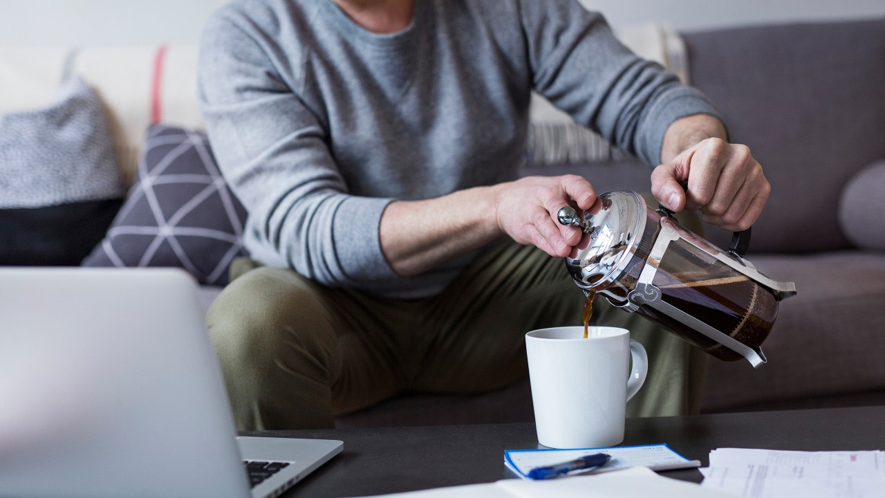 A man pouring coffee at home; image used for HSBC Investing in property page.