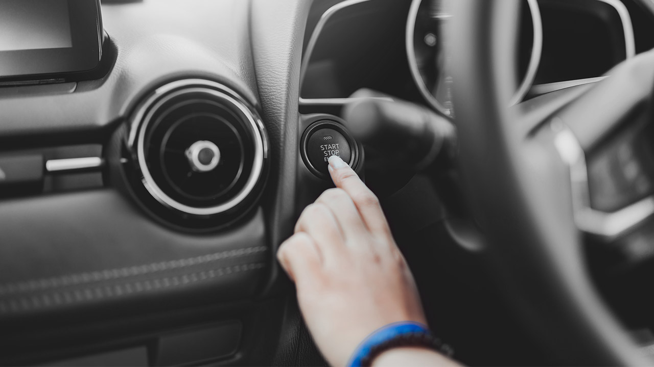 Pushing an engine start button of a car; image used for HSBC Australia car loan page.