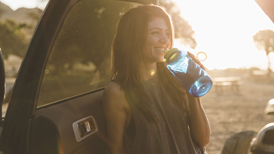 A woman drinking water outdoor; image used for HSBC car insurance page.