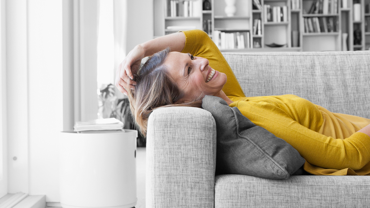 A smiling woman lying down on sofa; image used for HSBC Australia What is Balance transfer.
