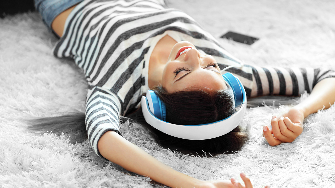 A woman listening music and lying down on a carpet; image used for HSBC Australia Instant savings.