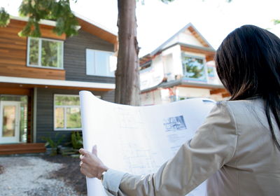 A woman looking at plans; image used for HSBC Buying and Selling Your Home page.