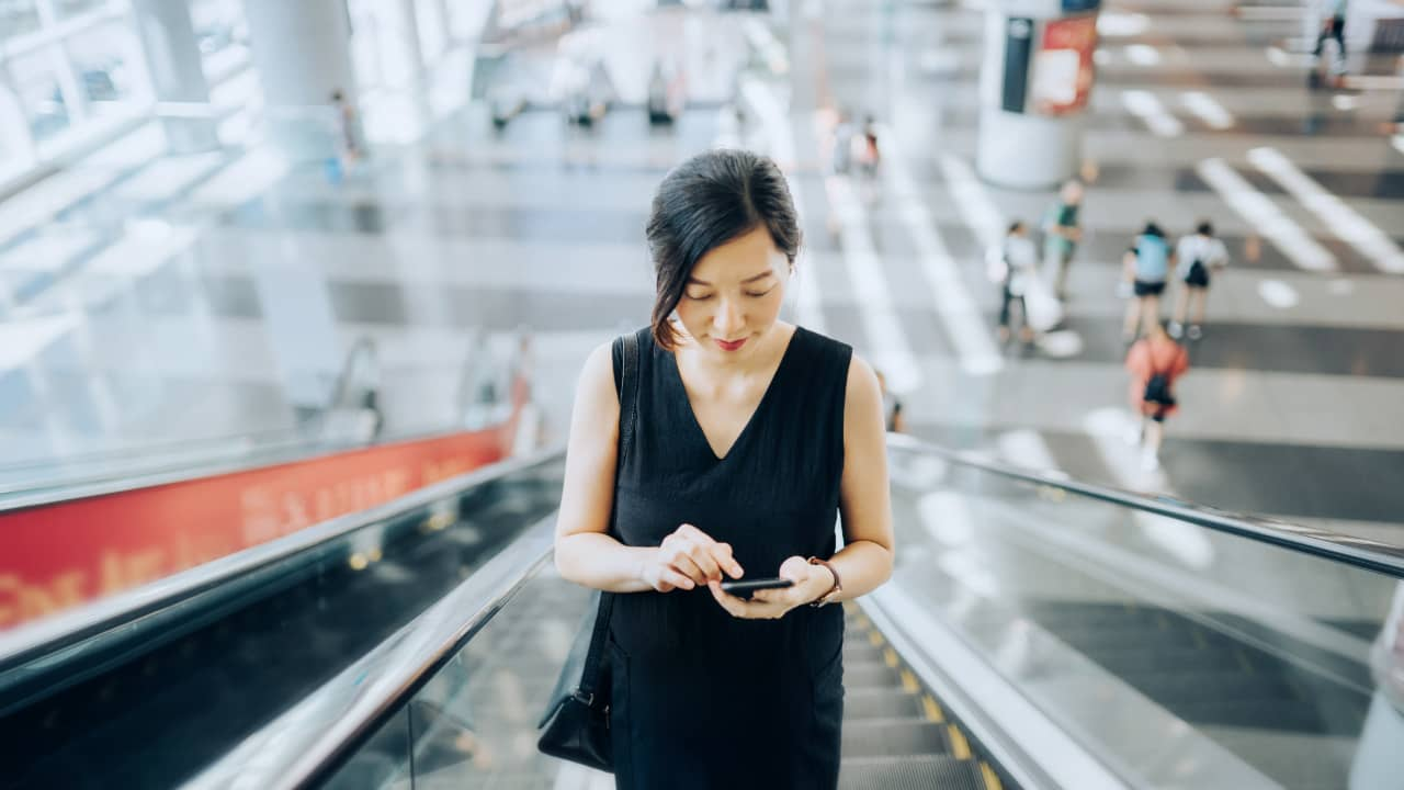 A woman checking on phone and going up by escalator