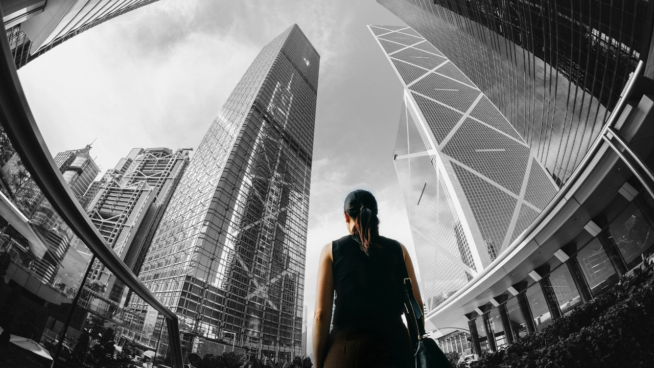 A woman standing in financial skycrapers; image used for HSBC Australia Exchange Traded Funds (ETFs).