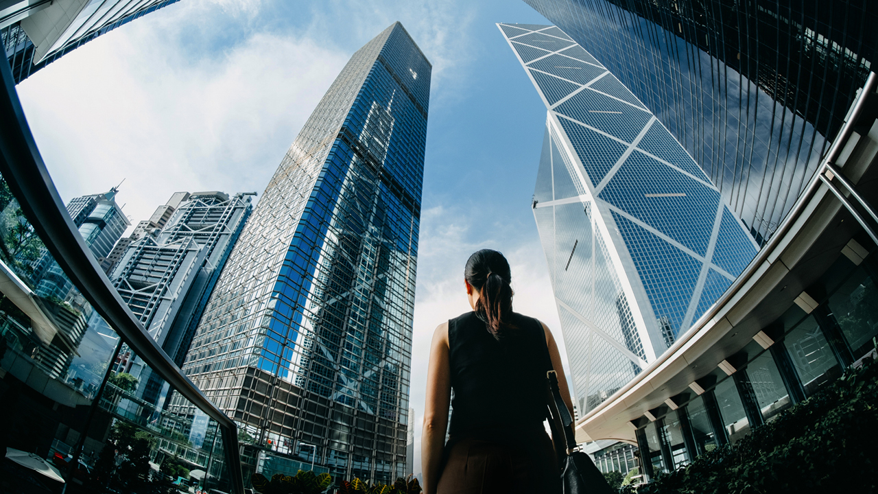 Woman standing between financial skyscrapers; image used for HSBC Australia Exchange Traded Funds (ETFs).
