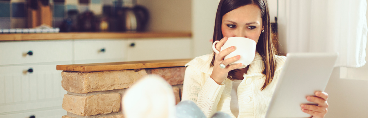 A woman drinking coffee and checking on iPad; image used for HSBC welcome to Start Smart.