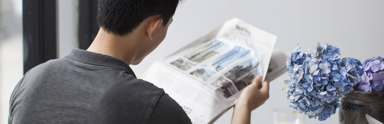 A man reading newspaper; image used for HSBC query transaction.