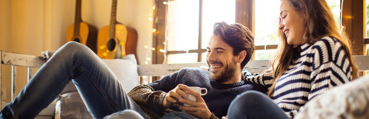 A couple is smiling in the sofa with coffee; image used for HSBC Australia Foreign currency accounts page.