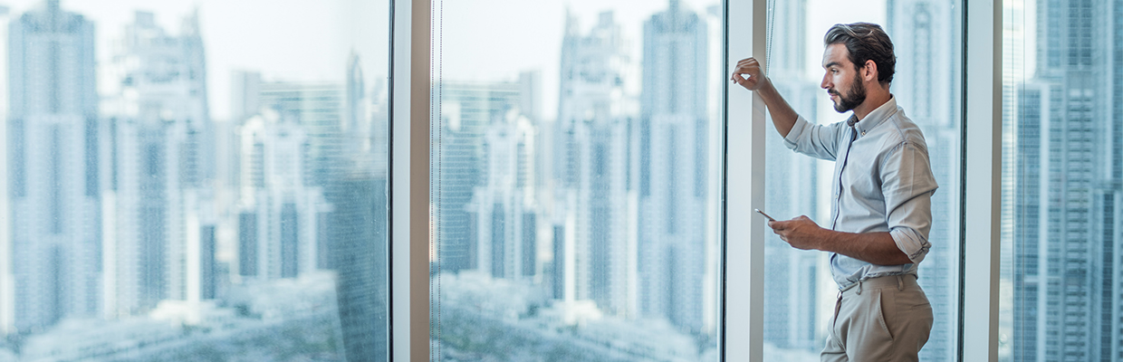 A businessman with smartphone staring through window with skyscraper view; image used for HSBC Australia online share trading.