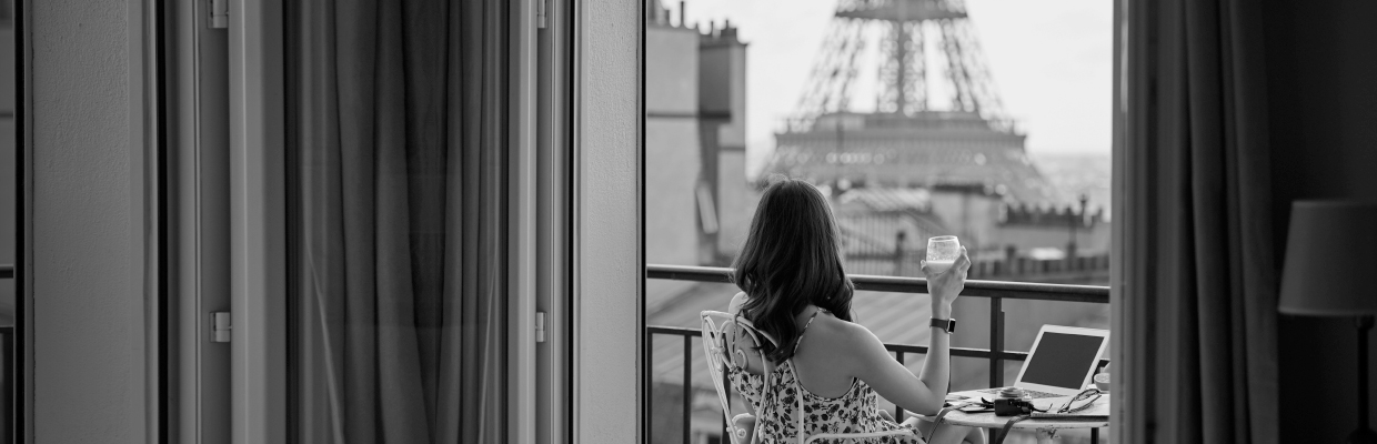 Woman holding a glass and sitting in a balcony near Eiffel Tower; image used for HSBC Australia Platinum qantas Credit Card page.