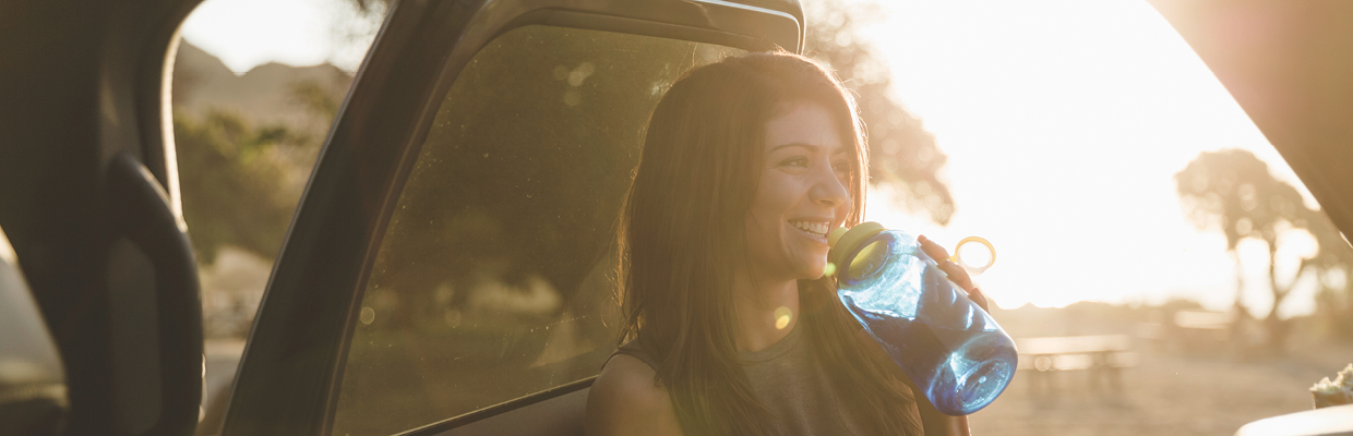Smiling woman drinking water outside her car; image used for HSBC Car Insurance page.